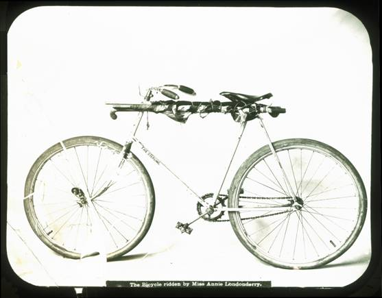 Annie began her trip on a 42-pound drop-frame (women's) Columbia bicycle ill-suited for long-distance travel, and attired in long skirts. When she reached Chicago in September 1894, the Sterling Cycle Works of Chicago offered her a men's Sterling weighing approximately 21 pounds. The men's frame meant that riding in skirts was no longer feasible and Annie took to wearing bloomers, and later a men's riding suit. The Sterling, like the Columbia, had a single gear and no free-wheel mechanism, which meant if the wheels were spinning the pedals were spinning, too. But unlike the Columbia, the Sterling had no brake. The device on the front wheel is a cyclometer, an odometer for bicycles. An American diplomat in Paris gave Annie the American flag wrapped around the frame. This photograph of Annie's bike was taken in San Francisco in early spring 1895.